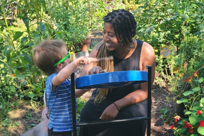 An image of a teacher smiling as she and a young child play the tin pan together in the garden