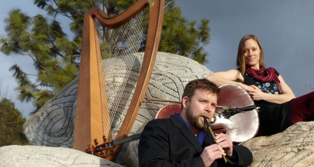An outdoor image of Neil and Christina of Crossbow, accompanied by the harp and cello, as Neil plays the flute